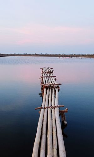 Wooden post in lake against sky during sunset