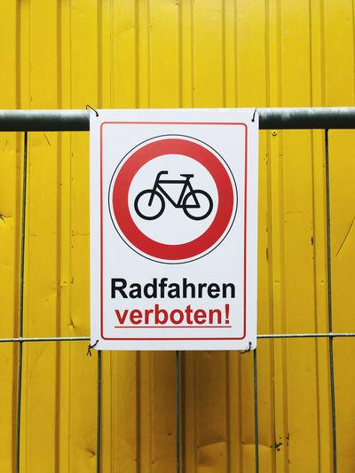 Close-up of warning sign on yellow wall