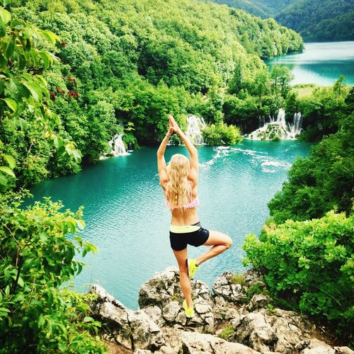 Full Length Rear View Of Woman In Tree Position On Rock By River In Forest