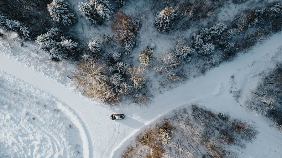 Aerial view of forest nountaiin winter with snowy trees. three to four roads with car in the middle.