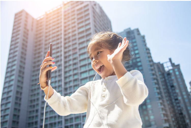cute asian kid selfie with mobile on urban city tower in background Architecture One Person Portrait City Building Exterior Built Structure Lifestyles Childhood Smiling Standing Real People Emotion Waist Up Casual Clothing Leisure Activity Building Happiness Child Office Building Exterior Skyscraper Outdoors Innocence Digital Composite Literacy Generations