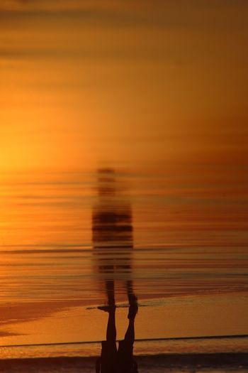 Upside down image of man with reflection on shore during sunset
