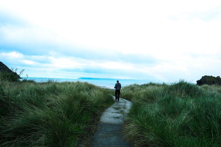 Rear view of man walking on land against sky