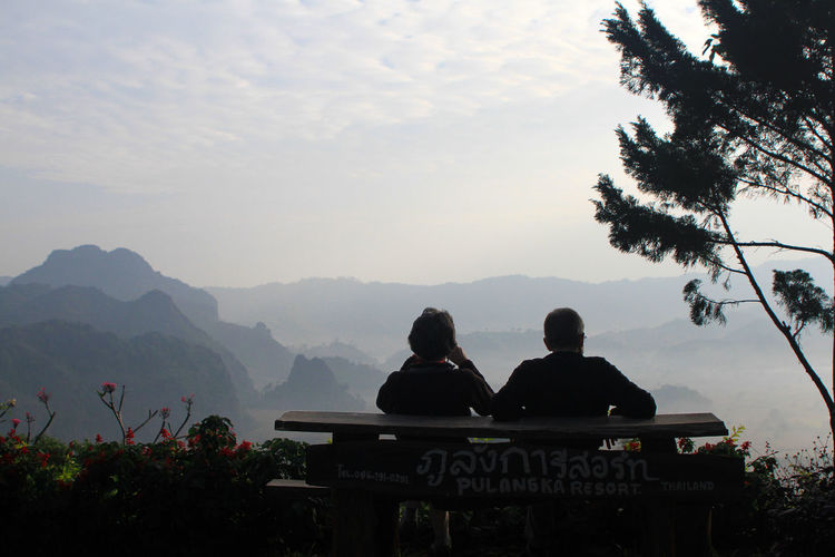 Rear view of silhouette people sitting against mountains