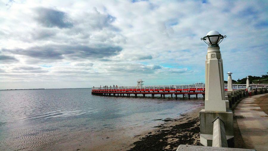 Footpath By Sea Against Cloudy Sky
