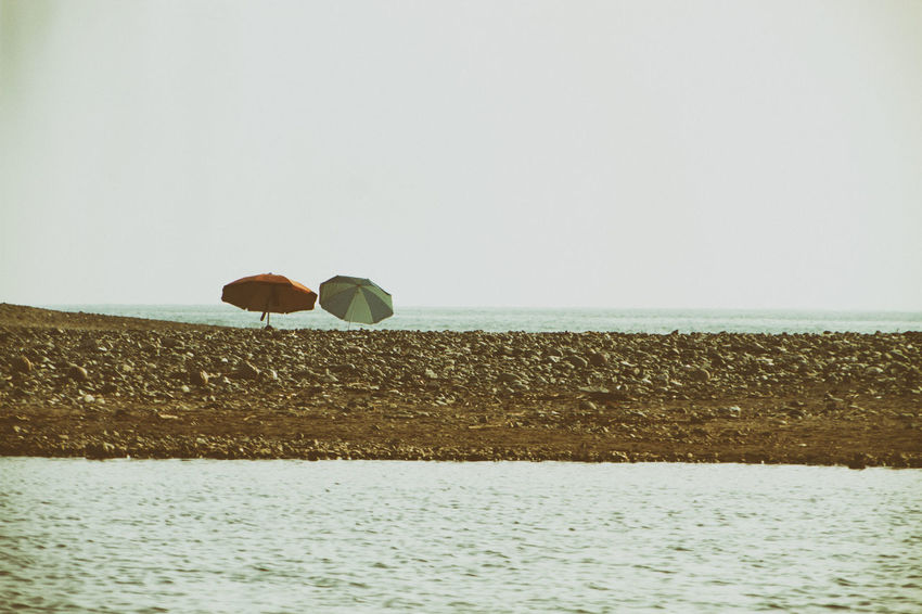 Two umbrellas shine on the shore of a rocky beach in the community of Nexpa, in Michoacan, in central Mexico. Nexpa Beauty In Nature Clear Sky Day Horizon Over Water Nature No People Outdoors Scenics Sea Sky Umbrella Water An Eye For Travel