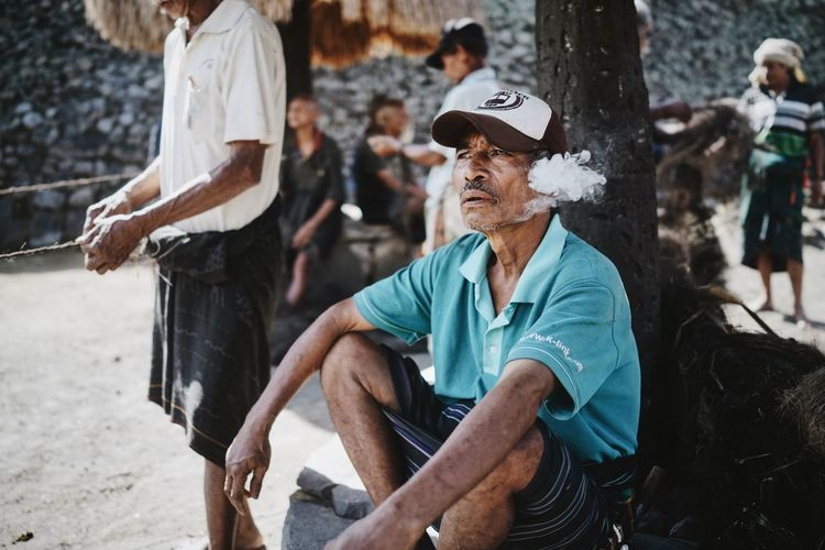 ASIA Baseball Cap Bena Blue Shirt Cigarette  Day Flores INDONESIA Man Men Nusa Tenggara Timur People Portrait Real People Senior Adult Senior Men Shadow Sitting Sitting On The Ground Smoking Taking A Rest  Traditional Village Travel Travel Photography Village Life The Portraitist - 2017 EyeEm Awards