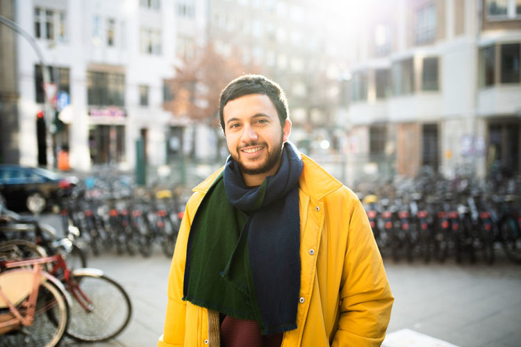Smiling Happiness Portrait City Looking At Camera One Person Young Adult Waist Up Emotion Transportation Adult Yellow Confidence  Clothing Street Outdoors Stylish Turkey Berlin Spring Raincoat City Life Bike Guy Street Style