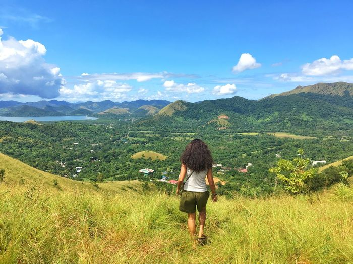 Rear view of woman walking on grass against mountains and sky