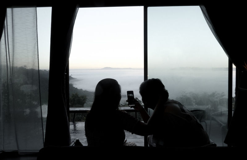 Rear view of people photographing through window