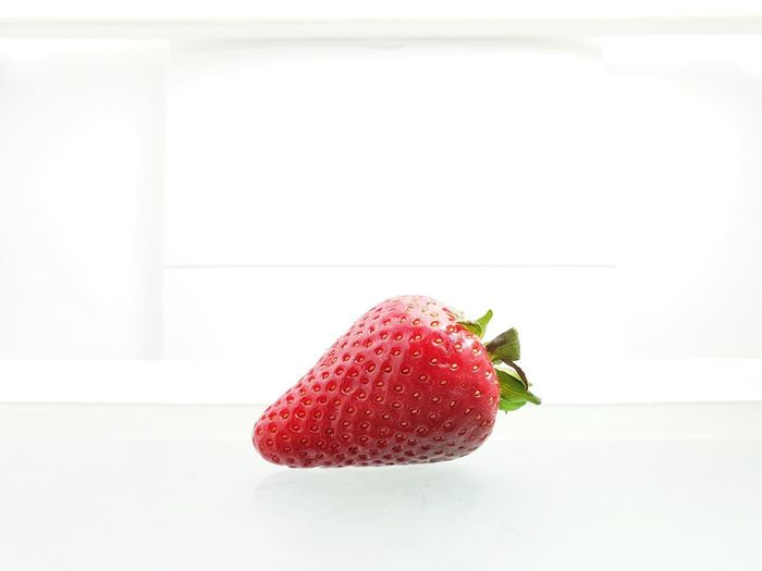 Close-up of strawberry on table against white background
