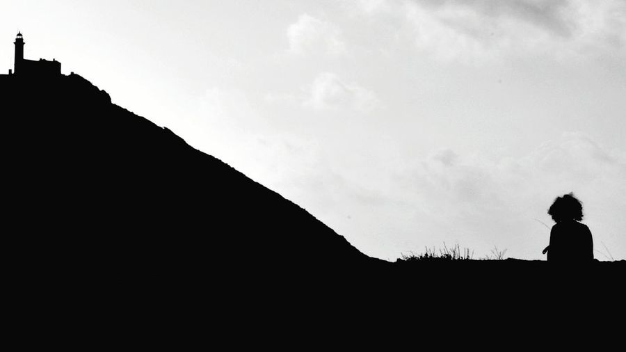 Silhouette man looking at mountain against sky