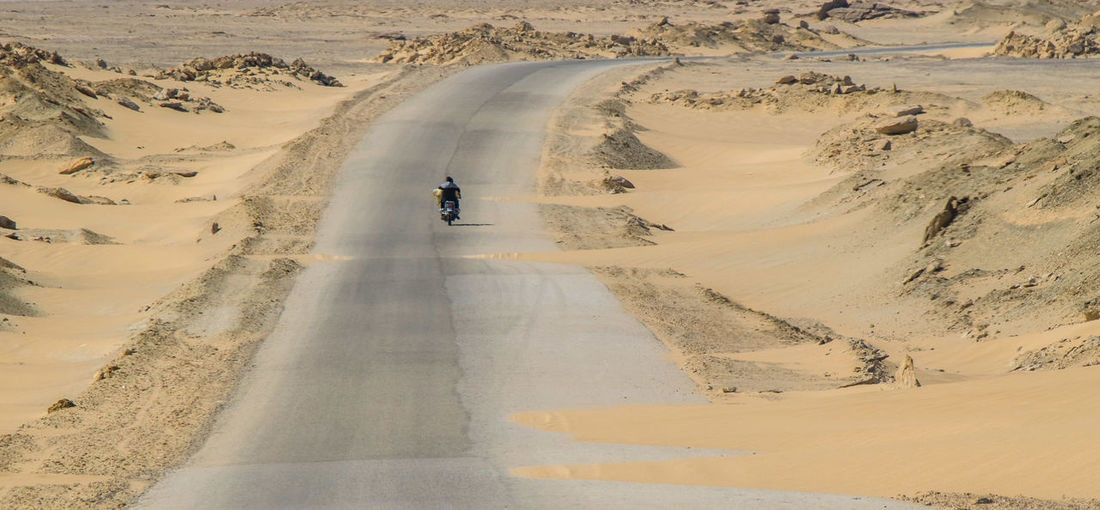 Rear View Of Man Riding Motorcycle On Road At Desert