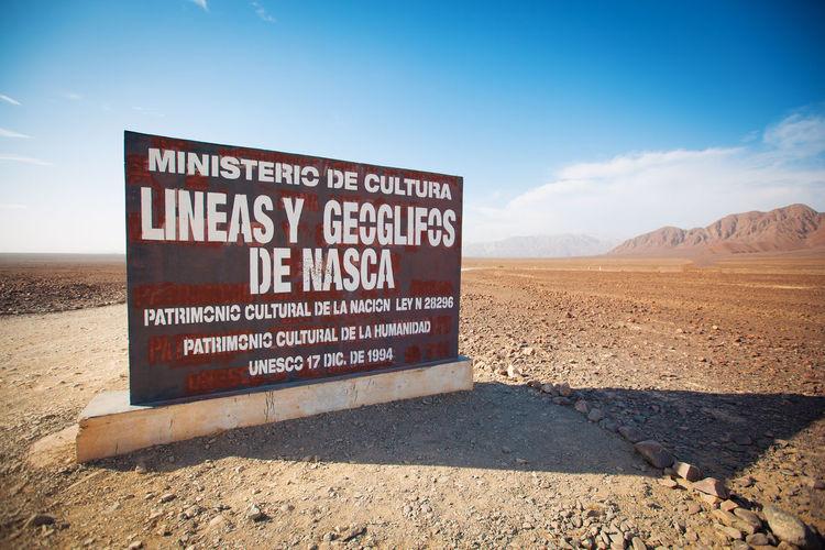 Information sign on desert against sky