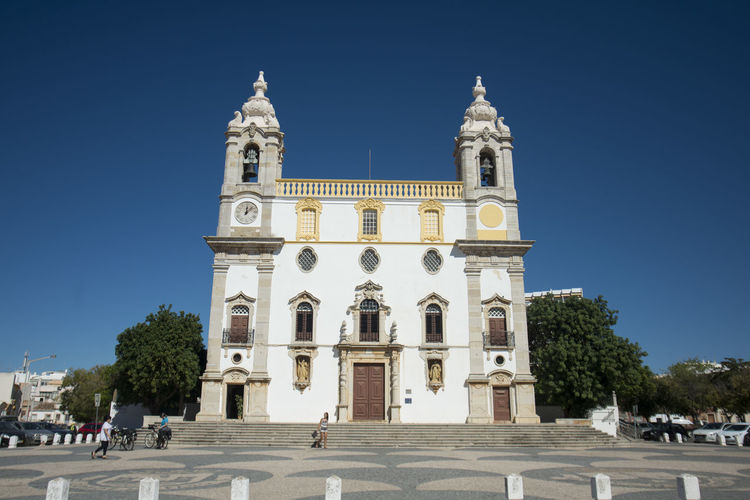Low angle view of igreja do carmo at faro against clear blue sky