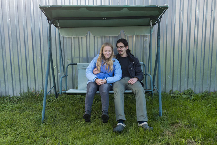 Smiling young couple sitting on swing outdoors