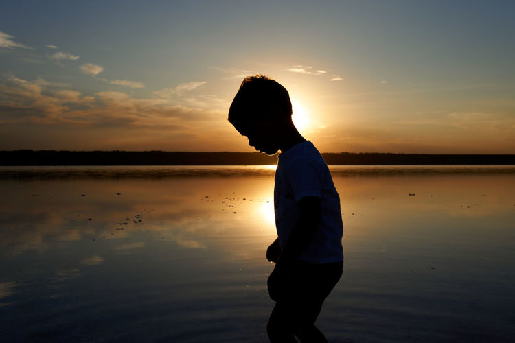 Child boy silhouette on the sunset time by the sea.