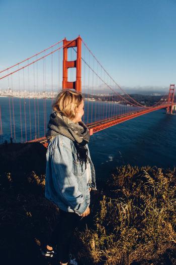 Woman standing against golden gate bridge