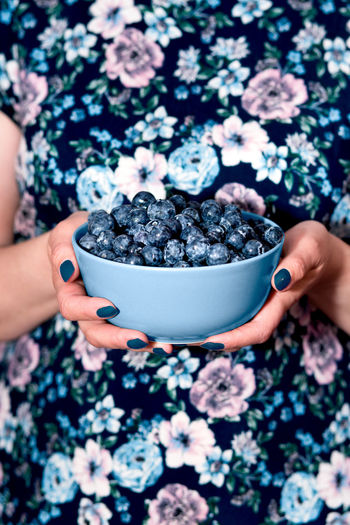 Close shot of female hands holding bowl filled with fresh blueberries. Woman wearing flowery blue dress standing at front of purple background. Front view, vertical shot. Berries Dessert Eating Freshness Life Woman Young Berry Blueberries Blueberry Enjoying Enjoyment Female Food Fresh Fruit Garden Girl Healthy Joy Organic Outdoors person Summer Sweet