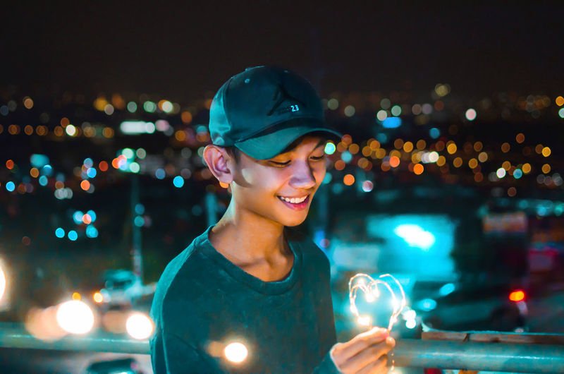 Portrait of smiling young woman against illuminated city at night