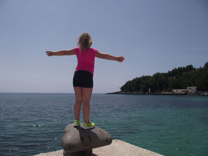Rear view of girl with arms outstretched standing at beach against blue sky