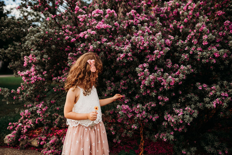 Woman standing by pink flowering tree
