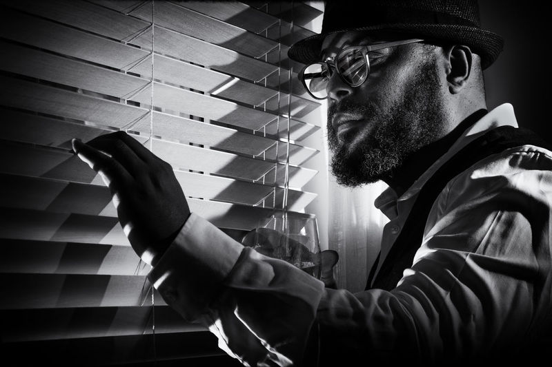 Close-up of man looking through window