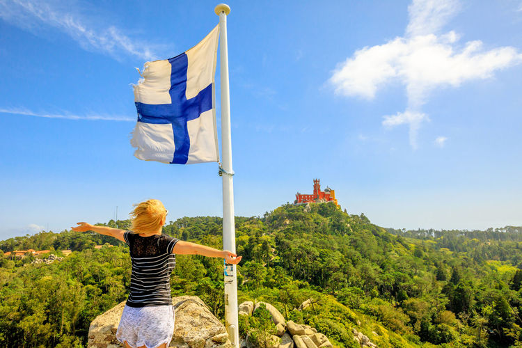woman traveler enjoying Sintra in Portugal Happy girl with open arms with Finland flag waving, Pena Palace National Monument and Unesco Heritage on top of a hill with sunset light. Portugal Sintra Castle Ruins Medioeval Cities Wall Tourism Flags Skyline Cityscape Palace Castle Ruin Aerial View Woman Flag Moors Castle Pena Palace Moors Sky Nature Real People Plant One Person Tree Day Patriotism Rear View Leisure Activity Cloud - Sky Lifestyles Architecture Built Structure Building Exterior Green Color Sunlight Outdoors Hairstyle Wind Looking At View