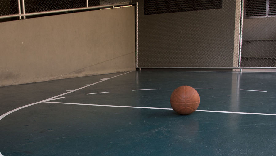 Close-up of ball on floor at court