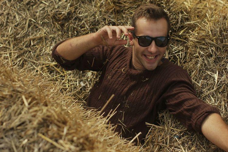 Portrait of man lying on grassy field
