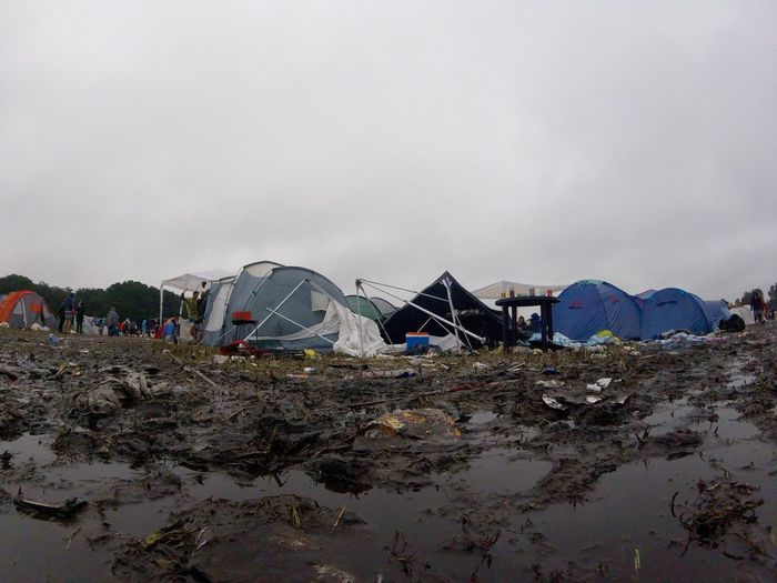 Muddy field by tents at campsite against clear sky