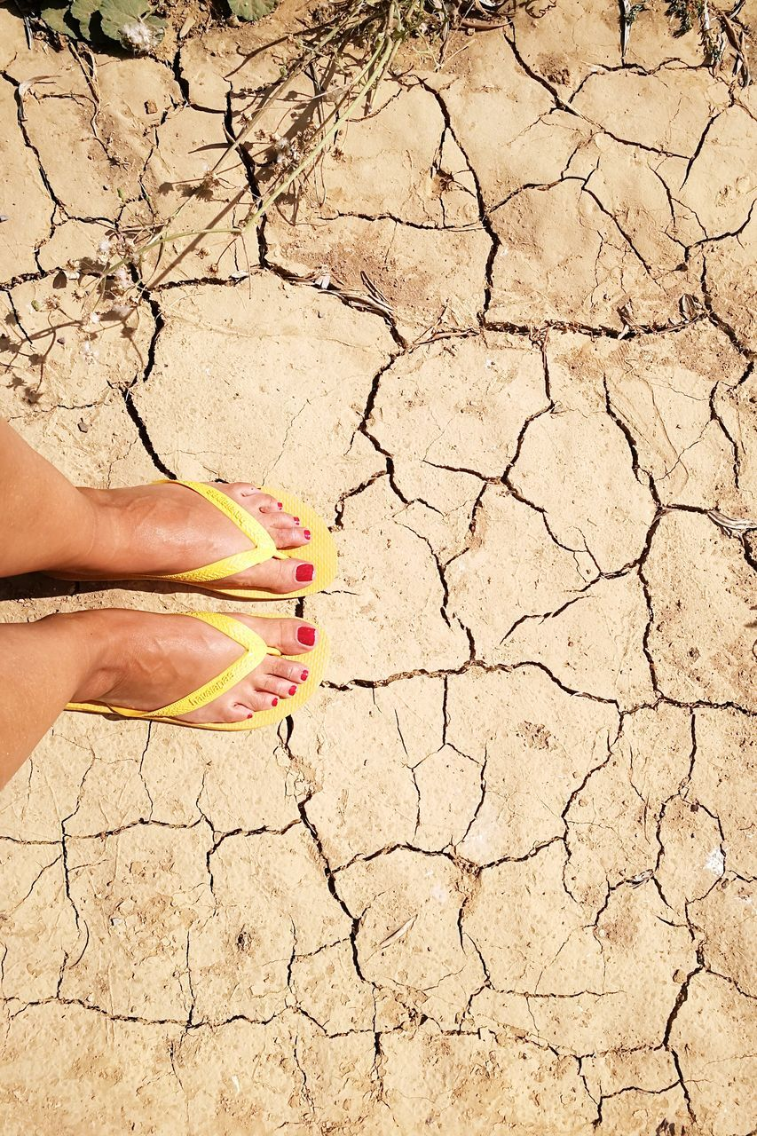cracked, human body part, one person, body part, drought, real people, arid climate, dry, climate, land, nature, high angle view, day, barren, low section, scenics - nature, environment, desert, dirt, outdoors, human foot, mud, finger