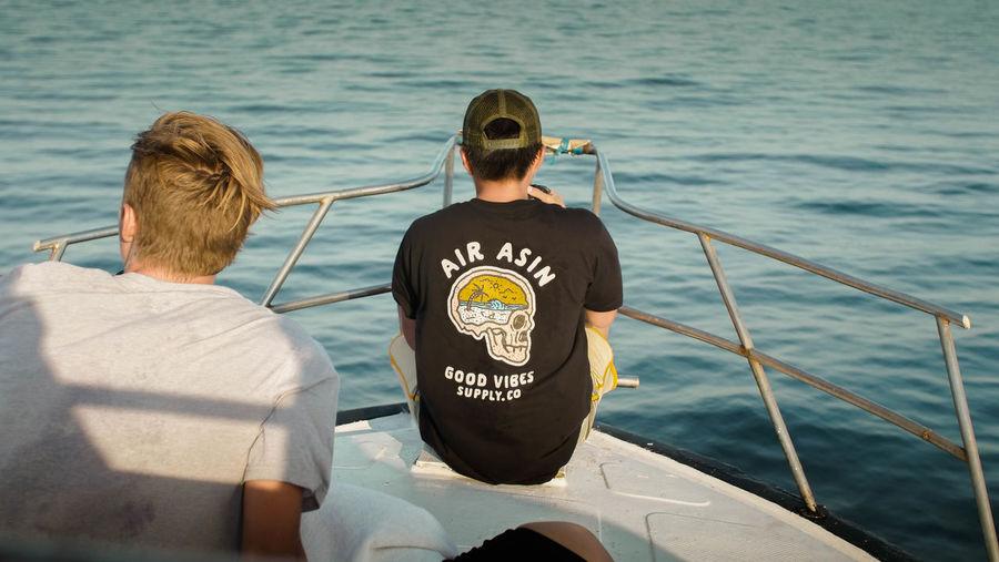 Rear view of men sitting on boat in sea