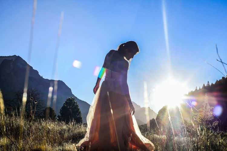 Woman standing on field against sky on sunny day