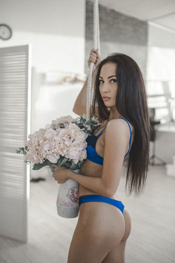 Portrait of sensuous female model holding bouquet while standing at home