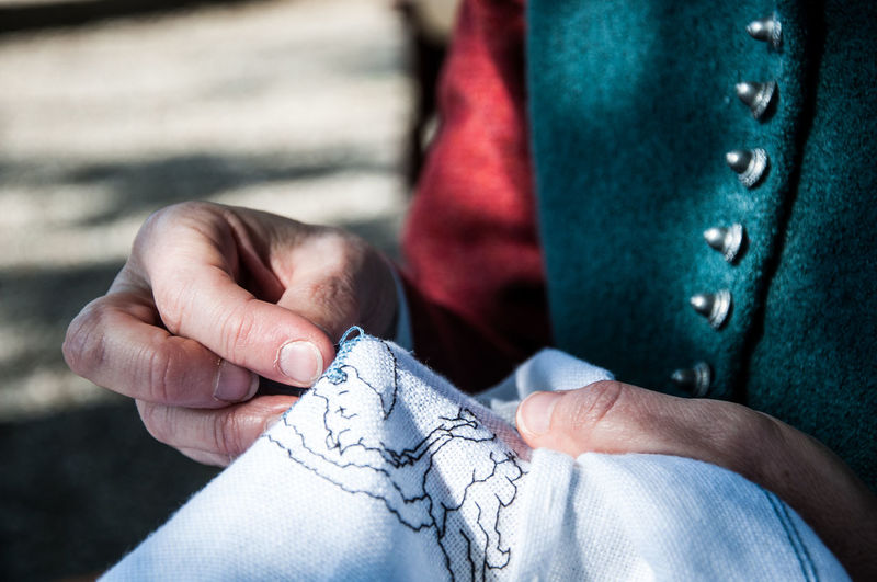 Midsection of person making embroidery on fabric