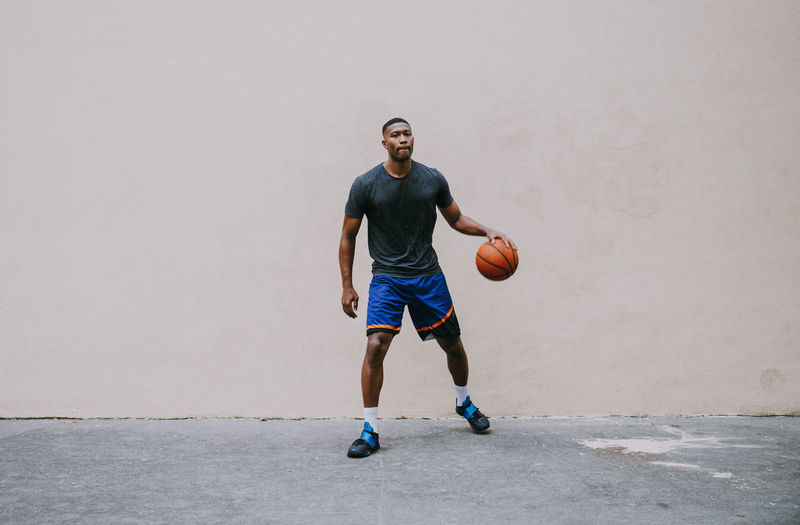 Full length portrait of young man playing basketball against wall