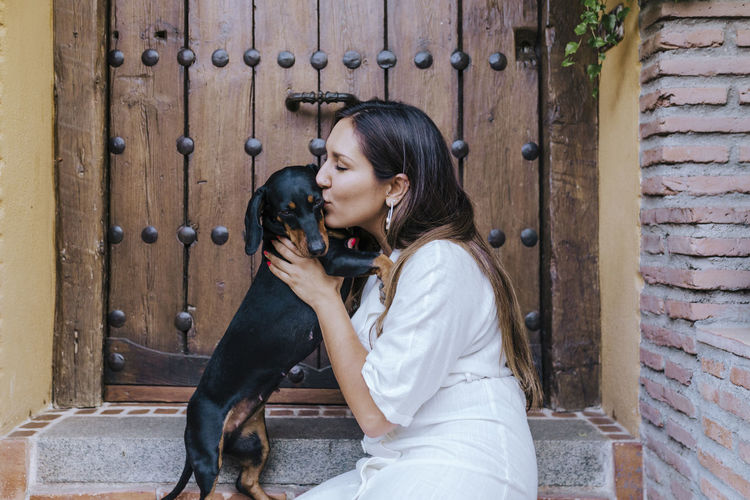 Side view of woman kissing dog while sitting at house doorway
