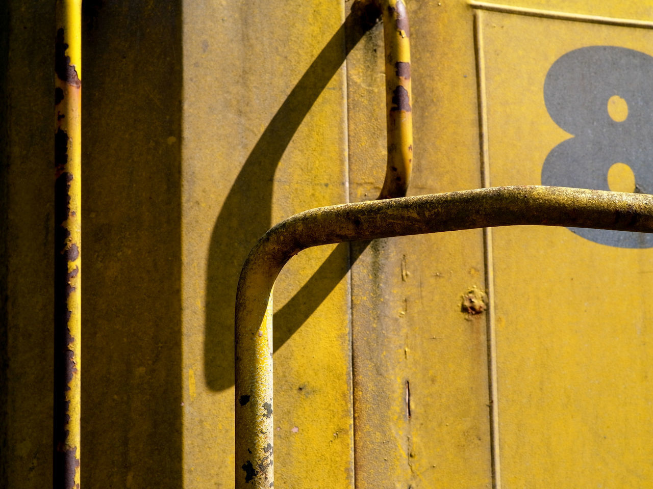 FULL FRAME SHOT OF YELLOW WALL WITH RUSTY METAL
