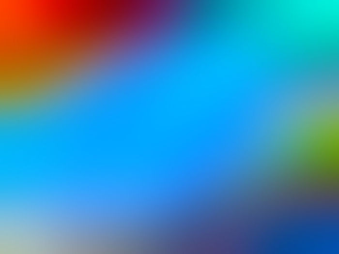 Defocused image of rainbow over blue background