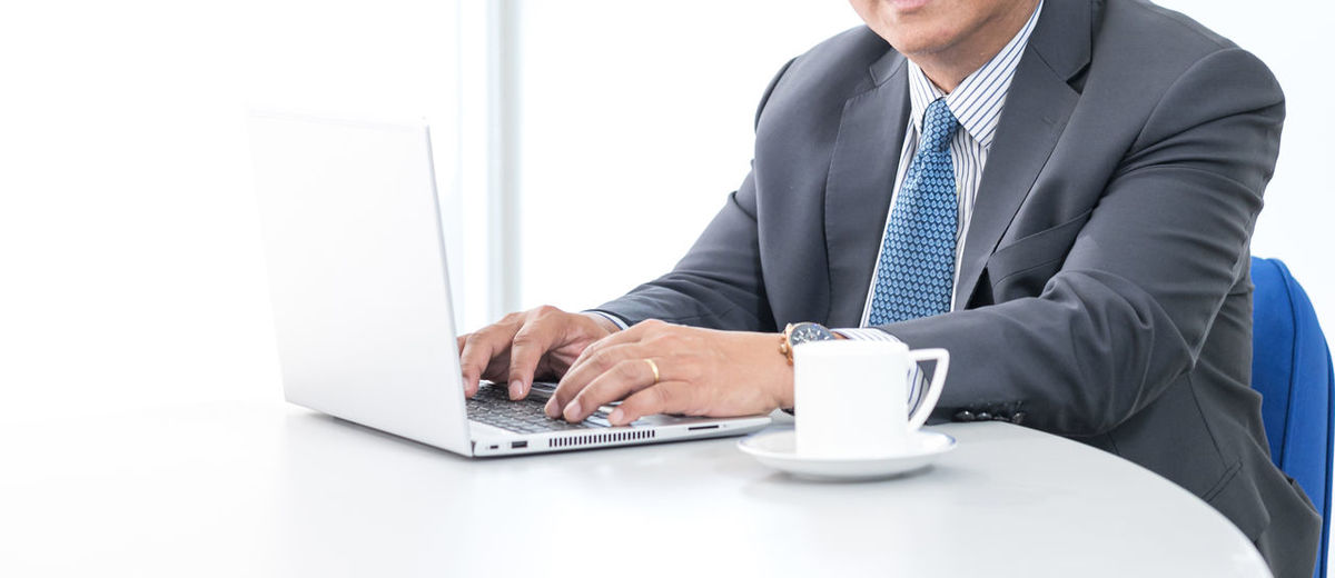 Midsection of man using laptop