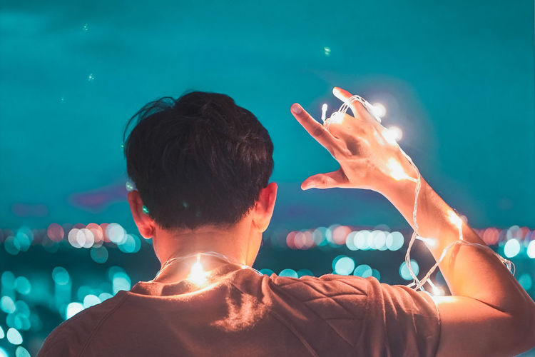 Rear view of man holding fairy light
