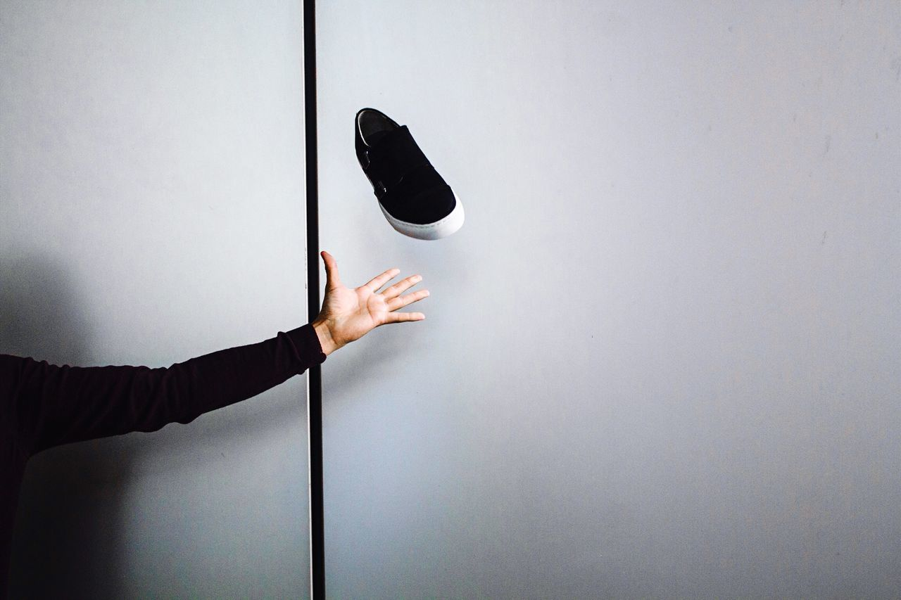 Cropped image of hand throwing shoe against wall
