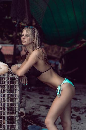 Side view of woman wearing bikini standing at beach