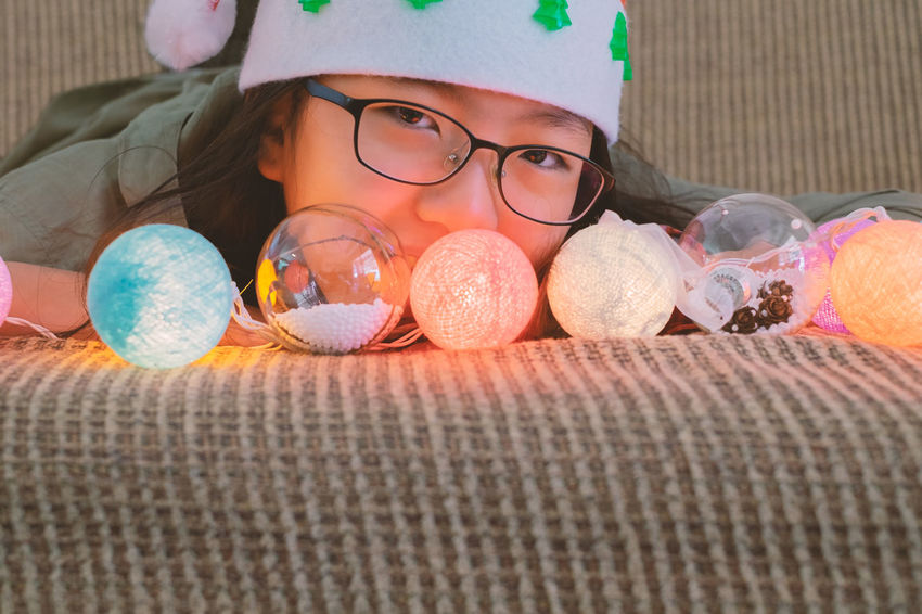 Childhood Child One Person Lying Down Indoors  Girls Glasses Eyeglasses  Portrait Front View Close-up Bed Lifestyles Innocence Leisure Activity Christmas Decoration Light Bulb Santa Hat Girl Kid Smile Face New Year Celebration