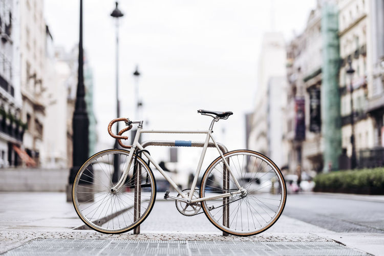 Bicycle parked on street against buildings