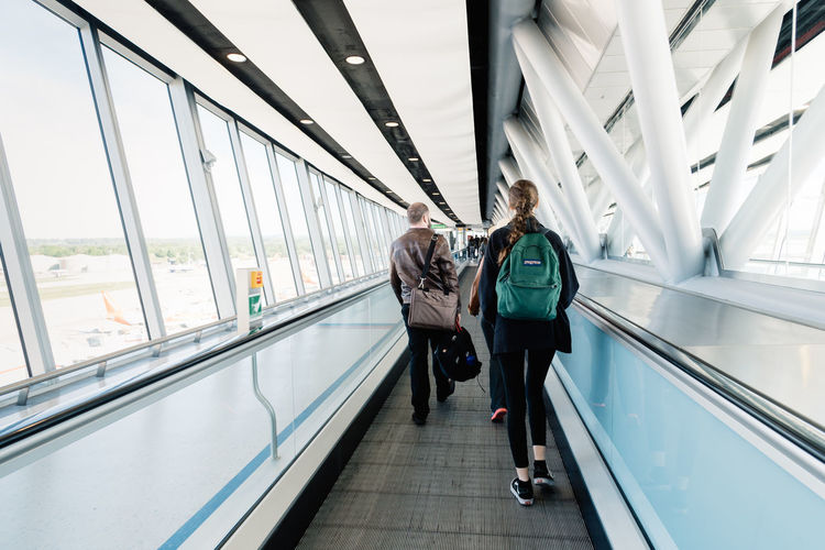 Passengers on moving walkway in the terminal of Gatwick Airport. Concept travel Brexit Corridor Gatwick London Uk Airport Architecture Autowalk British Business Concept England English Europe Future Hall Hallway Modern Moving Moving Pavement Moving Sidewalk Moving Walkway  Passenger People People-mover Speed Terminal Tourism Tourist Transport Transportation Travel Travelator Traveler Visitors Walkway Connection