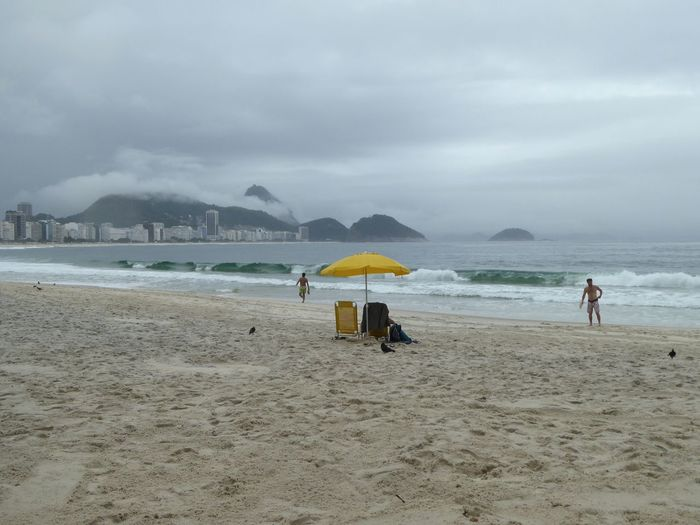 Beach Cloud - Sky Clouds Copacabana Beach Day Grey Color Nature Outdoors Rainy Days Rio De Janeiro Sand Sea Seascape Silent Moment Silhouette Two People Umbrella Water Waves Yellow