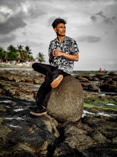 Full length of man sitting on rock looking away against sky