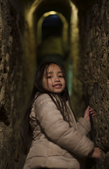 Portrait of girl standing amidst stone wall